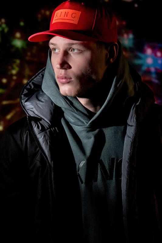 Model wearing black AW18 King Apparel jacket and crimson Manor snapback