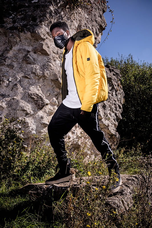 Fire Chulo wearing King Apparel citrus Blackwall down jacket and black Langdon tracksuit bottoms